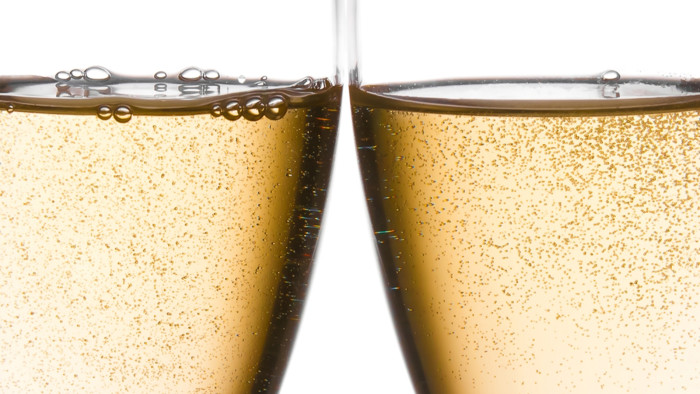detail of cheers with two champagne glasses with gold bubbles on white background; Shutterstock ID 122436274; PO: TODAY.com
